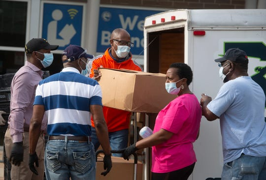 Escambia County Commissioner Lumon May, center, unloads meals outside the Theophalis May Neighborhood Resource Center on Saturday.