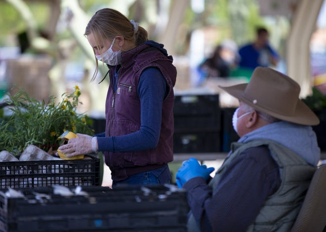 Lindsey Grolmes, left, and Frank Martin, Crooked Sky Farms owner, work the produce booth at Gilbert Farmers Market in Gilbert, Ariz., on Saturday, April 11, 2020.