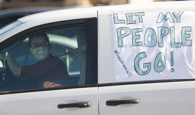 Protesters with signs on their vehicles wait to drive to the Eloy Detention Center on April 10, 2020. More than 100 cars in a caravan drove around outside the facility in protest of conditions and safety for inmates after cases of COVID-19 have been cropping up.