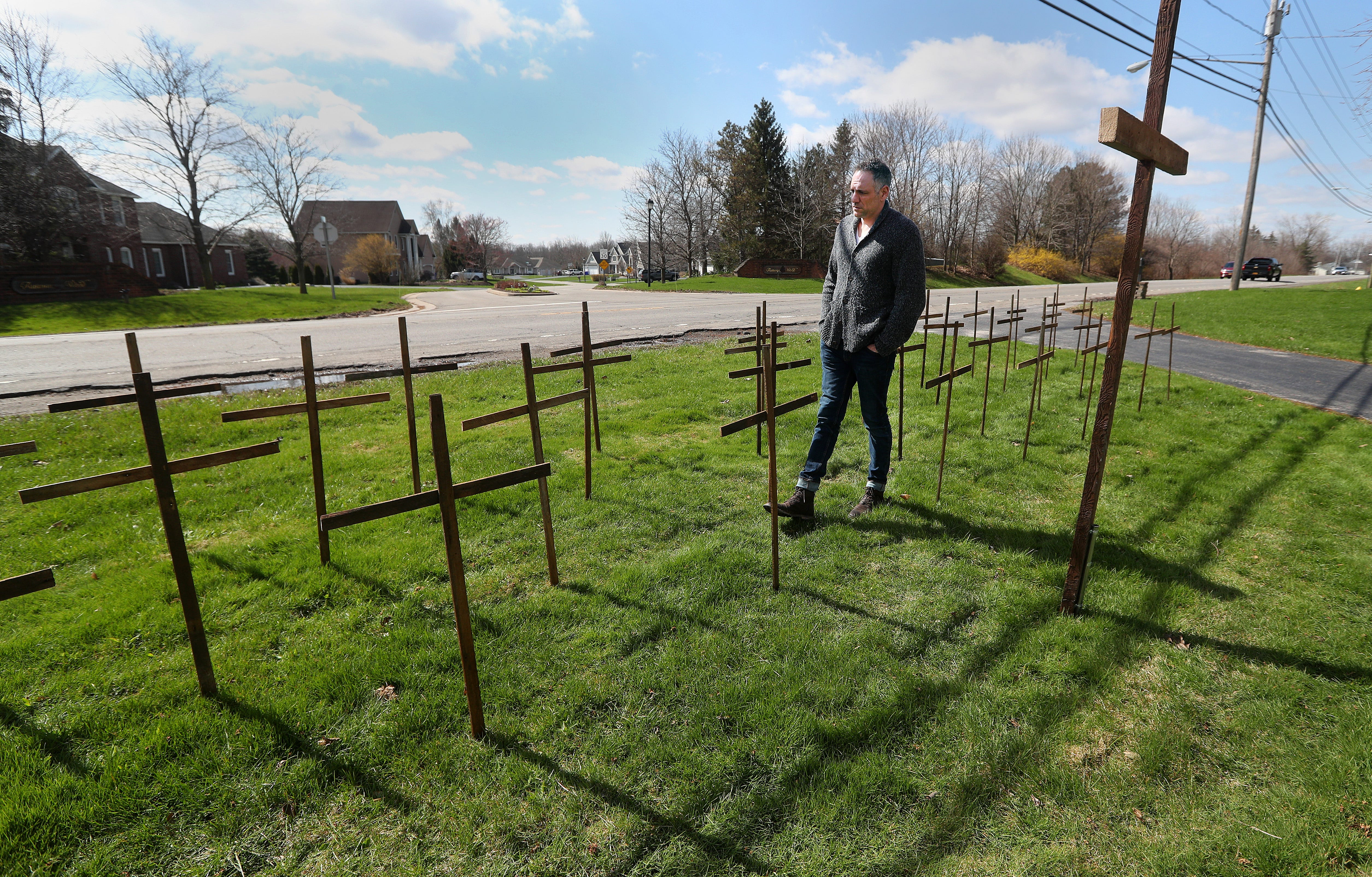 The virus continued its merciless path throughout 2020, claiming New Yorkers daily. In front of his Chili home in April, Jim Corbett walks through the rows of wooden crosses he's placed for each person in Monroe County who has died of COVID-19.