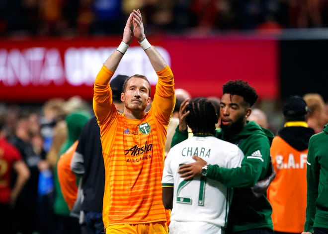 FILE - In this Dec. 8, 2018, file photo, Portland Timbers goalkeeper Jeff Attinella, center left, looks to the fans as midfielder Diego Chara (21) is consoled following their loss to Atlanta United FC in the MLS Cup championship soccer game in Atlanta. Attinella is also a children's book author, with five titles to his credit. He writes Dr. Seuss-style rhymes about his favorite sporting events, publishing them through his own company. He's now offering free downloads of the books while families are quarantining because of the coronavirus.