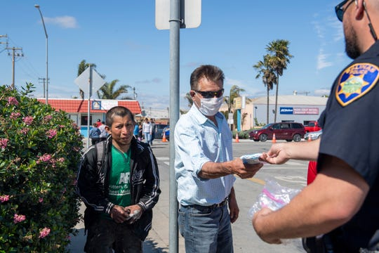A Salinas Police Department officer hands face mask packets to people walking in during the mask distribution event on Friday, April 10, 2020.