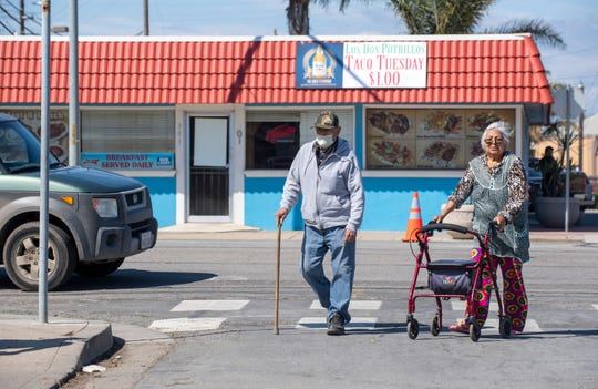 An elderly couple crosses the street to get in line for the mask distribution event that was organized by a group of Stevenson School parents on Friday, April 10, 2020.