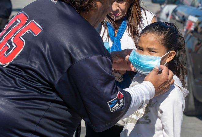 Anthony Henderson le pone una mascarilla a su hija después de recibirla del Departamento de Policía de Salinas el viernes 10 de abril, 2020.