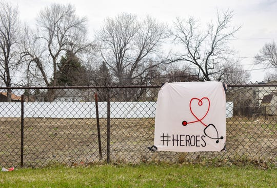 A sheet honoring medical staff working to fight the coronavirus hangs on a fence across from the Avera hospital on Saturday, April 11, in Sioux Falls.