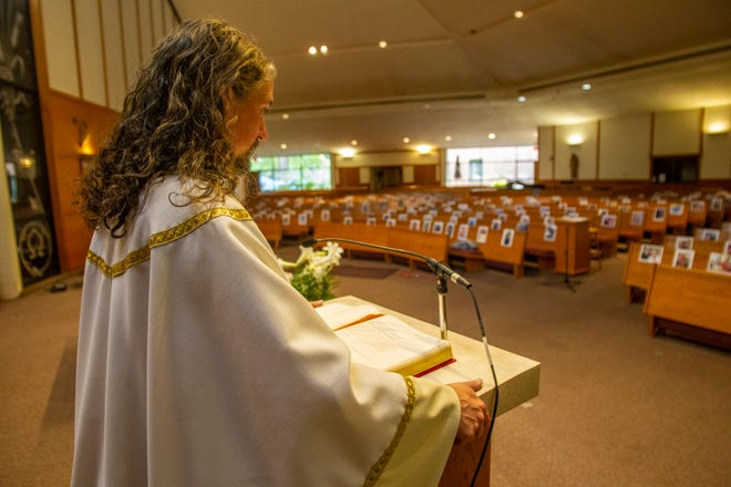 Father Tom Dillion, a priest at Good Shepherd Catholic Church, preaches to an empty sanctuary with pews covered in photographs of the congregation, Saturday, April 11, 2020.