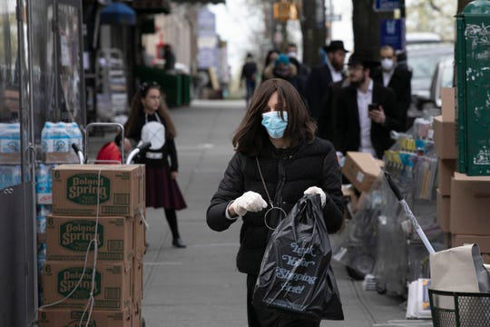 A woman wearing a mask and gloves leaves Kahan's Superette, which specializes in kosher foods, in the Crown Heights neighborhood of Brooklyn, Tuesday, April 7, 2020 during the coronavirus pandemic in New York. The Jewish holiday of Passover begins Wednesday, April 8. (AP Photo/Mark Lennihan)