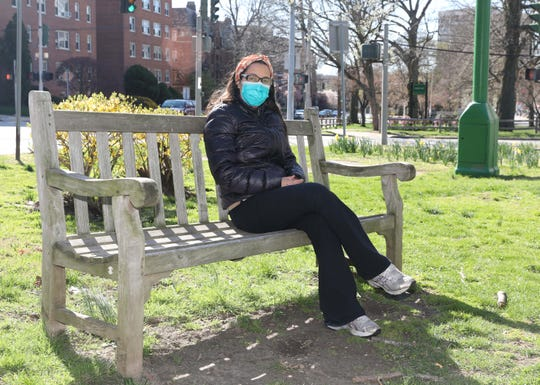 Claudia Go, a healthcare professional, is pictured at Tibbets Park in White Plains, in front of a row of apartment condos and cooperatives on North Broadway, April 11, 2020.
