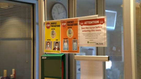 Signs hang outside the entrance to a COVID-19 patient's room reminding health care workers of the personal protective equipment necessary to enter the room.