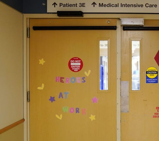 """The words """"Heroes at Work"""" hang on the doors leading to Christiana Hospital's Medical Intensive Care Unit."""