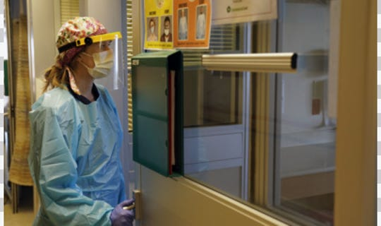 A ChristianaCare nurse looks into the room of a patient in Christiana Hospital's Medical Intensive Care Unit.
