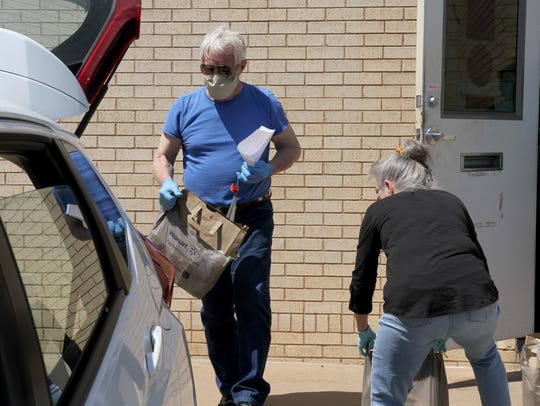 George Senn places groceries in the back of a car to deliver Friday, April 10, 2020, outside Interfaith Outreach Services.