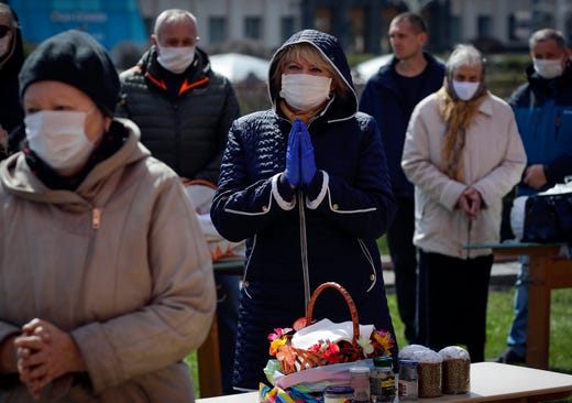 Catholic believers, wearing face masks and practicing social distancing to protect from coronavirus, are blessed by priest outside a church as religious services continue in Minsk, Belarus, Saturday, April 11, 2020. The Catholic community in predominantly Orthodox Christian Belarus prepare to celebrate the resurrection of Jesus Christ on Easter Sunday. The new coronavirus causes mild or moderate symptoms for most people, but for some, especially older adults and people with existing health problems, it can cause more severe illness or death.