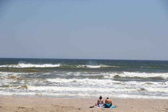 Two people sit on the beach on North Padre Island on Easter Sunday, April 12, 2020.