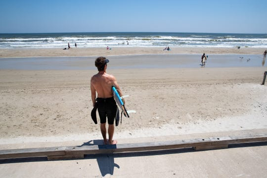 A surfer stands on the North Padre sea wall as he looks out on to the beach on Easter Sunday, April 12, 2020.