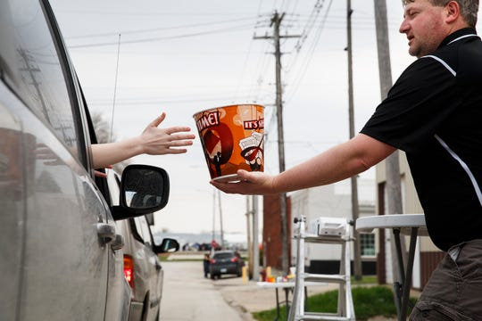 Neal Crawford of Stuart delivers a bucket of popcorn from the Stuart Fremont Theatre as residents of the town turn out for a Scoop the Loop event on Saturday, April 11, 2020, in Stuart.