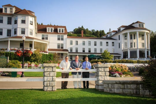From left, Victor Callewaert, his son Todd Callewaert and grandson Andrew Callewaert stand in front of The Island House Hotel in 2018. The hotel, built in 1852, is the oldest hotel on Mackinac Island. Reservations are steadily flowing in for the 2020 summer season.