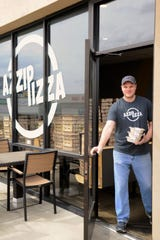 Trevor Long of the Evansville West Azzip Pizza location heads to the curb with P Fresh Kitchen meals on Tuesday, Apr. 7, 2020.