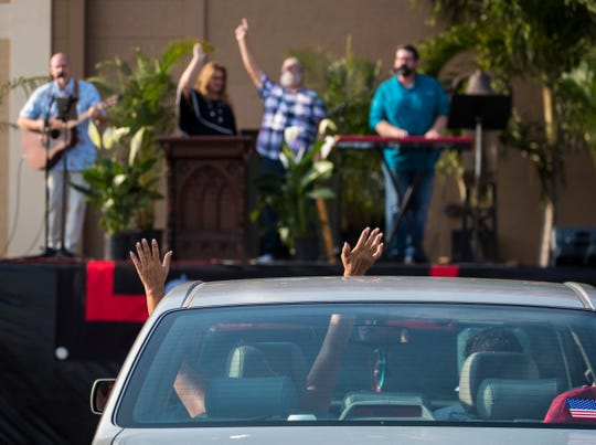 Emily Caguana participates from inside her vehicle during Sunday's Easter Service at Cape Vineyard Community Church in Cape Coral, April 12, 2020. The service, which was held outdoors at a large parking lot, was broadcast over FM radio for patrons attending and also streamed live online for those at home. In an effort to minimize exposure to the coronavirus, churches are using alternative methods to congregate more safely.    ​