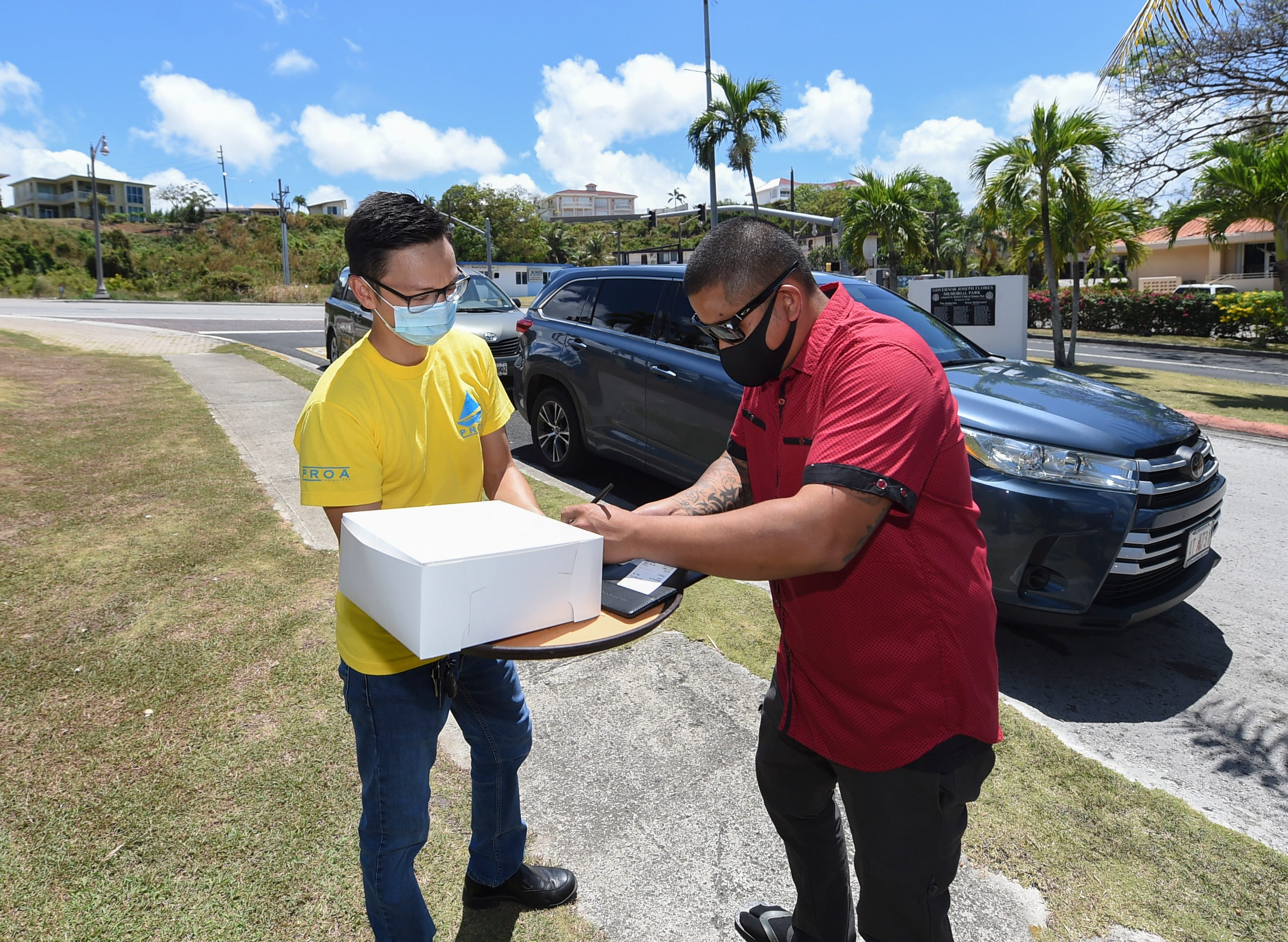 Proa Restaurant employee Vince Mendiola, left, serves Paul Muña his taro cheesecake order outside the Tumon eatery on April 12, 2020. Muña ordered the cheesecake to bring back home for a quarantined Easter celebration with his family.