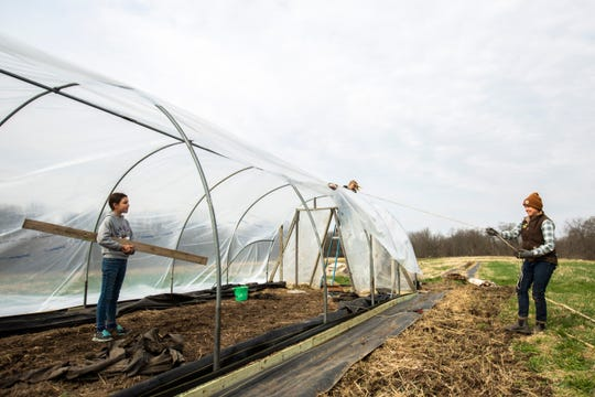 Liliona Roller, left, talks with Molly Schintler, far right, as Saige Turner, center on ladder, holds down the plastic covering while they set up a greenhouse, Saturday, April 11, 2020, at the Echollective Farm in Mechanicsville, Iowa.