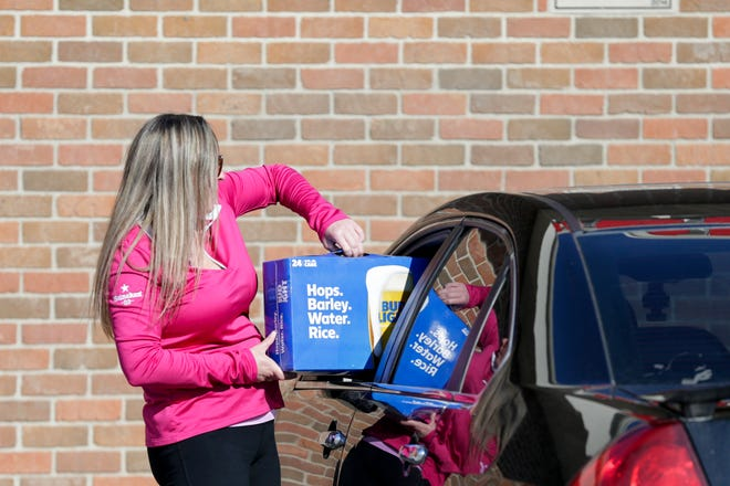 Michelle Perry hands a customer their order through their car window at Bedrock Liquors, 5853 Indiana 43, Friday, April 10, 2020 in West Lafayette.