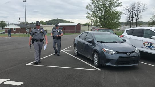 Kentucky State Troopers take down license plate numbers of people attending an in-person Easter service at Maryville Baptist Church in Hillview, Kentucky.