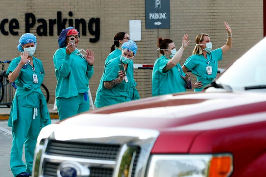 Piedmont Athens Regional Medical Center health care professionals stand and wave from the sidewalk as a caravan of well-wishers parades around the hospital in Athens, Ga., on April 5. Amid the coronavirus pandemic, Americans across the country are finding creative ways to thank hospital employees and first responders.