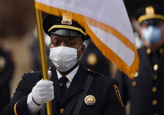 A member of the color guard holds a flag prior to the arrival of the hearse that carries the body of Frank Scorpo, a  34-year-old motorcycle officer who had been hospitalized for more than 10 days with the coronavirus, outside of Police Head Quarters in Paterson, NJ on 04/12/20.