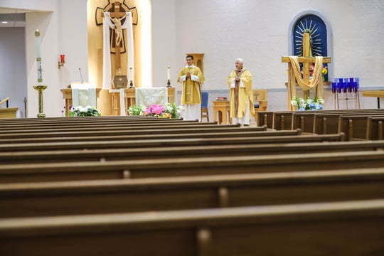 Rev. Richard Catanach conducts a live stream of Easter mass in a nearly empty auditorium at the Holy Cross Catholic Church in Las Cruces on Sunday, April 12, 2020, after Bishop Peter Baldacchino canceled all masses in the area due to Coronavirus concerns.