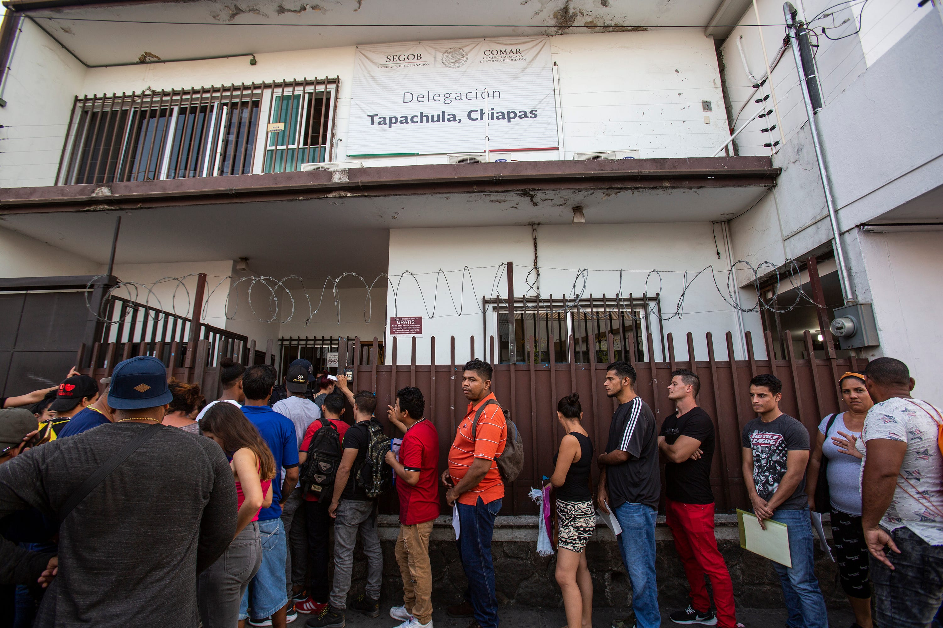 Migrants from diverse nations line up for interviews with the Mexico's commission for refugees, known as COMAR, in Tapachula, Mexico, in late February 2020. Many of the immigrants were seeking refuge in Mexico in order to safely continue their trek north towards the U.S.-Mexico border.