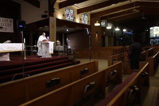 Reverend Monsignor Howard Lincoln of Sacred Heart Catholic Church celebrates Easter mass live on KMIR-TV due to California's stay-at-home order during the coronavirus outbreak on Sunday, April 12, 2020 in Palm Desert, Calif.