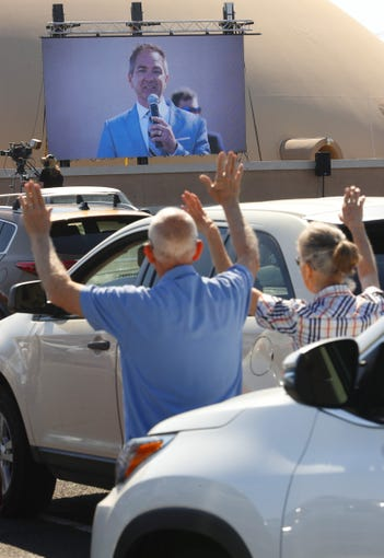 Charlie and Stacy Derouen raise their hands as they listen to Pastor Jason Anderson during an Easter drive-in service at the Living World Bible Church in Mesa on April 12, 2020.
