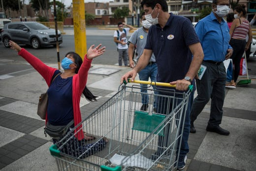 A man pushing a shopping cart asks a woman kneeling in prayer to get out of the way because she is obstructing people trying to get into a supermarket, in Lima, Peru, Saturday, April 11, 2020. The woman was praising God for cleansing the earth of heathens using the new coronavirus.