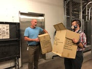 Dave Watt and Mars Sarossy carry boxes of condom shipments upstairs, where they'll wait to be shipped across Arizona and southern Nevada.