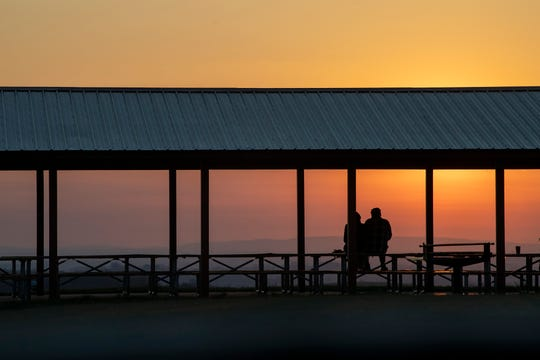 A couple watches the Easter sun rise from a picnic pavilion at Samuel Lewis State Park in Lower Windsor Township.
