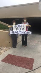 "Two WellSpan employees stand by a parking garage at York Hospital, holding a sign that reads ""Honk For Healthcare"" in honor of their co-workers who provide care for those stricken with the coronavirus."