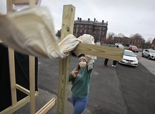 Joanna Coan prepares the large cross that is set next to the stage for a special Easter Sunday drive in service held by Calvary Chapel Center City at the Auditorium Center parking lot in Rochester April 12, 2020. Due to the coronavirus pandemic, the church plans to hold services in the parking lot each Sunday at 10 am. For more information go to: www.ccdriveinchurch.com