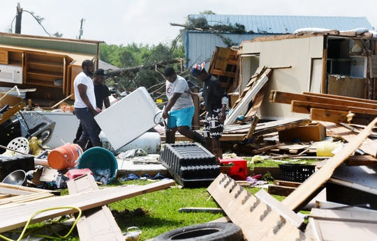 Dexter Fuller, left, removes the washing machine with the help friends from the remains of his parents destroyed home from the storm in the Kingston-Frierson area of DeSoto Parish.