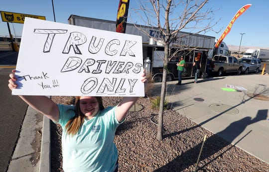 Maggie Williams with Big Mike's BBQ & Wings holds up a sing at a truck stop at in interchange along Interstate 70 between Grand Junction and Fruita, Colo., in April 2020. (Christopher Tomlinson/The Grand Junction Daily Sentinel via AP)