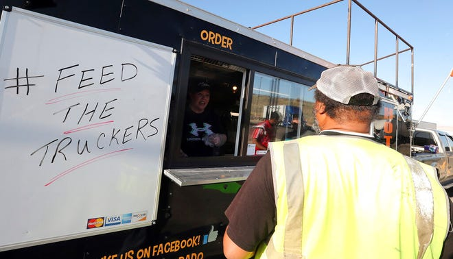 Al long-haul trucker at the Pilot truck stop at an interchange on Interstate 70 between Grand Junction and Fruita, Colo., stops for barbecue from Mike's BBQ & Wings, as Jamie Williams takes an order in April 2020. (Christopher Tomlinson/The Grand Junction Daily Sentinel via AP)