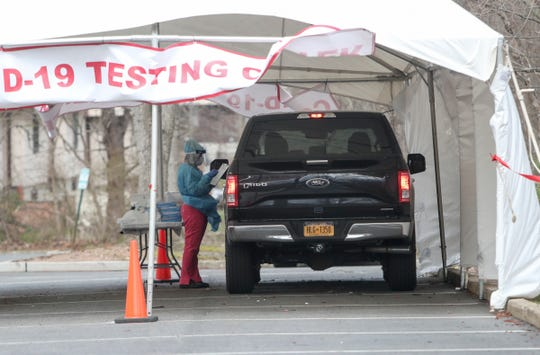 A medical professional administers a COVID-19 test inside a tent at a drive up test site in the parking lot of 20 Squadron Blvd. in New City on Friday, April 10, 2020.