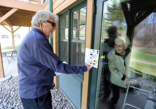 "Rick Bausé of Hopewell Junction, NY., shares an Easter card with his mother Marjorie, 96, a resident at Atria on Hudson, an assisted living facility in Ossining, N.Y., during an Easter morning visit April 12, 2020. Bausé has been having what he calls ""window visits"" with his mother at least once a week since the start of the coronavirus pandemic."