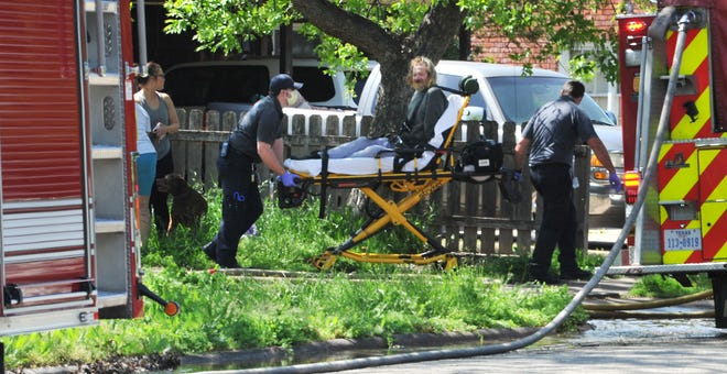 AMR medics work to transport a fire victim Sunday afternoon after the fire department responded to a reported house fire in the 4800 block of Alamo Drive.