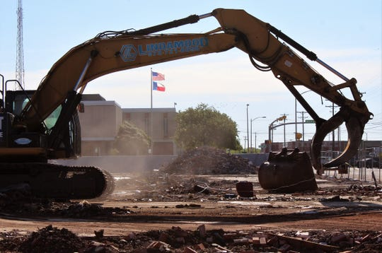 The U.S. and Texas flags whip in a brisk northerly wind Monday morning downtown as work continues to clear the site of the former Civic Plaza Hotel, which has been reduced to rubble. City Hall now can be seen from Pine Street.