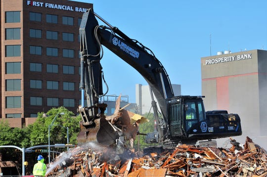 The view from Walnut Street toward downtown now is unobstructed as the Civic Plaza Hotel has been reduced entirely to rubble. An excavator works atop a pile of hotel remnants that eventually will be scooped into a dump truck for hauling.