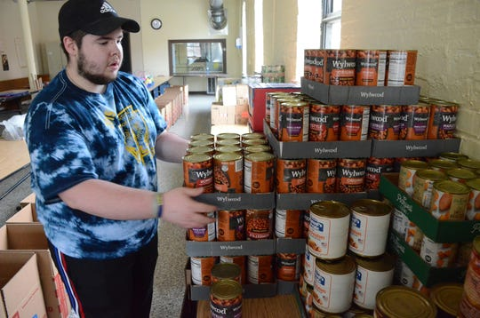 Chancelor Gillem of Battle Creek was packing boxes with food. Trace Christenson/The Enquirer