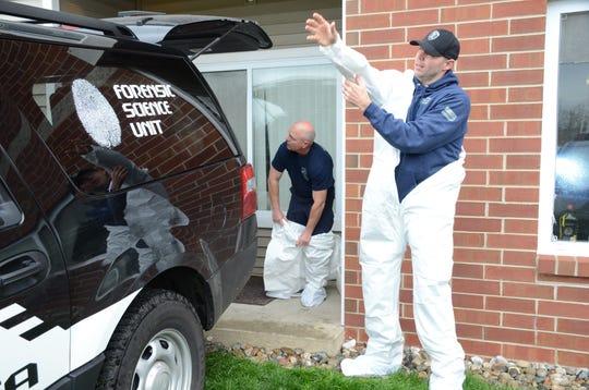 Crime Laboratory Supervisor Todd Rathjen, left,  and Corporal Andrew Olsen prepare to enter the apartment Monday.
