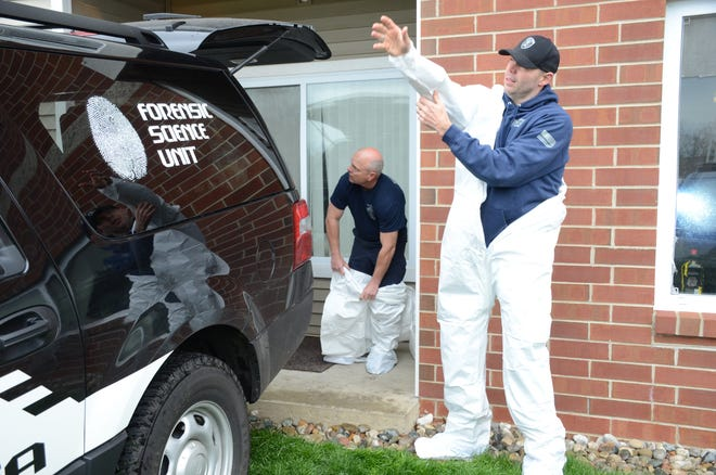 Crime Laboratory Supervisor Todd Rathjen, left,  and Corporal Andrew Olsen prepare to enter the apartment Monday.