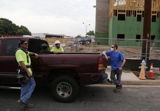 Jesse Martinez, left, Jacob Esparza and Phillip Eckwahl talk Thursday near a construction site on Briarcliff Boulevard in East Austin on Thursday.